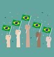 hands holding up brazil flags vector image vector image