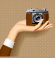 womans hand with retro photo camera vector image