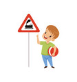 cute boy pointing finger at triangle road sign vector image vector image