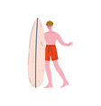 Male surfer standing on beach with surfboard