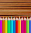 Palette pencils on wooden background vector image