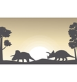 Silhouette of two triceratops on the hill scenery vector image