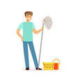 young smiling man cleaning the floor with a mop