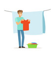 young smiling man hanging wet clothes out to dry vector image vector image