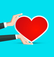 red paper heart in human hands on blue background vector image vector image