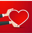 heart in human hands on red background vector image