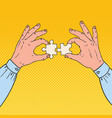 pop art male hands holding two puzzle pieces vector image vector image