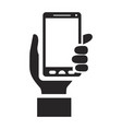 black silhouette of hand holding smartphone vector image
