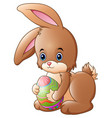 cute little bunny holding decorated easter egg vector image