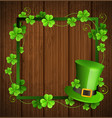 clover leaves and green hat on a wooden background vector image vector image