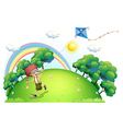 A boy playing with his kite at the hilltop vector image vector image