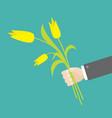 Businessman hand holding bouquet yellow tulip