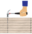Hand with a hammer and wooden board vector image