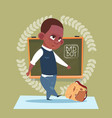 small bad school boy standing over class board vector image vector image