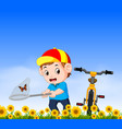 young boy with bicycle catching butterfly vector image vector image