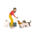 friendly female volunteer feeding dogs in animal vector image vector image