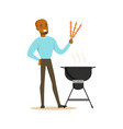 smiling african man preparing meat kebabs on a vector image vector image