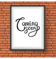 Coming Soon Texts in a Frame Hanging on Brick Wall vector image