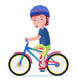 boy rides a bicycle in a protective helmet vector image vector image