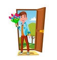 young guy in the open door with flowers and gift vector image vector image