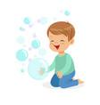Happy boy kneeling playing bubbles