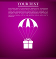 gift box flying on parachute on purple background vector image vector image