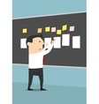 Businessman pinning sheets of paper on blackboard vector image vector image