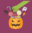 green zombie hand holding halloween pumpkin basket vector image