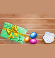 colored easter eggs cake and gift box on wooden vector image vector image