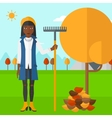 Woman with rake near tree and heap of leaves vector image vector image