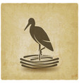 stork stands on one leg in nest vintage background vector image vector image