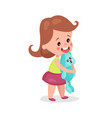 adorable little girl standing and hugging her vector image vector image