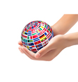 Flags of the world on a globe held in hands vector image vector image