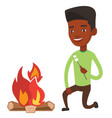 man roasting marshmallow over campfire vector image vector image