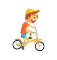 funny little boy in yellow baseball cap riding vector image