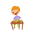 cute redhead boy eating soup on the dining table vector image