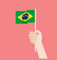 hand holding up brazil flag vector image vector image