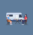 couple sitting at table near camping family vector image vector image