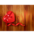 Red heart-shaped gift box with ribbon on wooden vector image