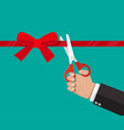 hand with scissors cut red ribbon vector image