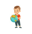 cute little boy holding globe kid protecting vector image vector image