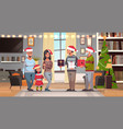 multi generation family in santa hats holding gift vector image vector image