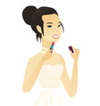 young asian bride paints lips with red lipstick vector image vector image