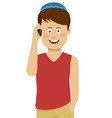 jewish boy wearing blue bale talking on the phone vector image vector image