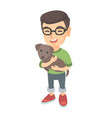 caucasian happy boy in glasses holding a dog vector image
