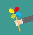 businessman hand holding paper windmill pinwheel vector image