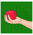 hand holding red apple on green background vector image