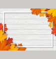 Autumn leaves and frame on white wooden background