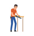 man cutting wooden plank using saw home vector image