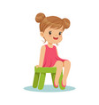 beautiful little girl sitting on a small green vector image vector image
